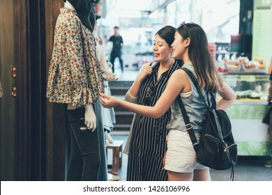 Two female shopaholic friends gazing at lady clothes wear on dummy model. sisters spend leisure time on weekend buying dress prepare for coming summer. women touching discussing about shirt hong kong