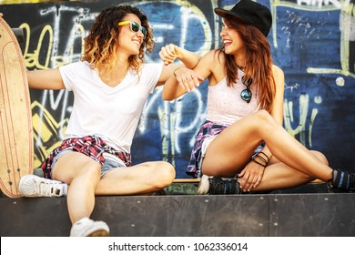Two female skaters friends sitting on ramp and hangout at the skate park .Laughing and fun.