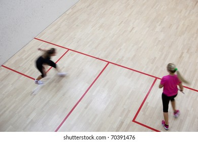 Two female squash players in fast action on a squash court (motion blurred image; color toned image)