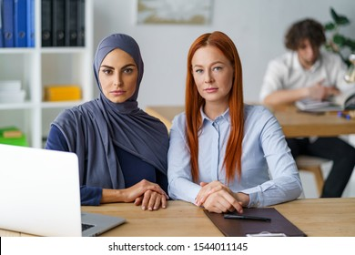 Two female students sitting at the desk during a class. Multi-ethnic people, social inclusion and higher education.