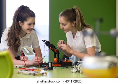 Two female students are working together in school to build a functioning robotic arm.
