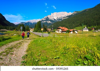 Two female tourists walking scenic path in Dolomite valley.