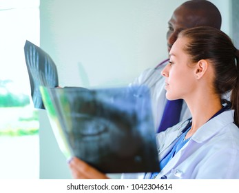 Two female women medical doctors looking at x-rays in a hospital.