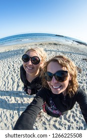 Two female young adult friends take a fisheye selfie at the beach on a sunny day