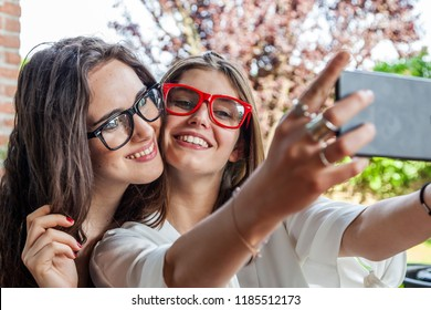 two female young friends take a selfie hugged together outdoors with funny faces