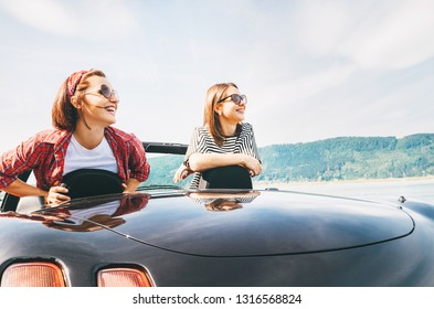 Two females friends traveling by Convertible car, have a stop brake to enjoy a mountain landsxapes