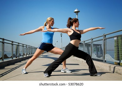 two females stretching on a pier