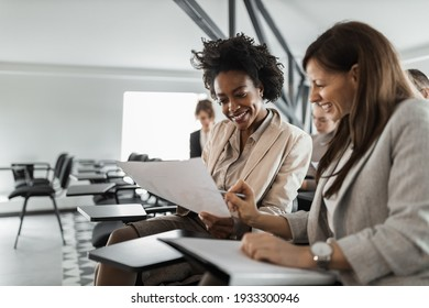 Two females in a suits, doing paper work.