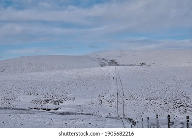 two fences creating a long corridor on snow covered plains of Scottish hills with a hillwalker in the distance following a footpath