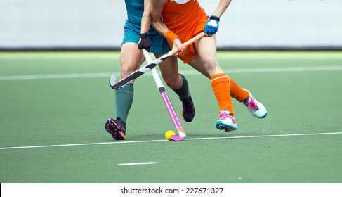 Two field hockey player, fighting for the ball on the midfield during an intense match on artificial grass