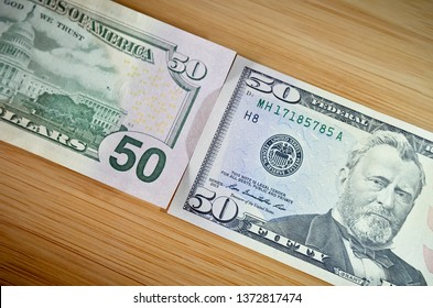 Two Fifty Dollar Bills Laid Diagonally on a Wood Surface