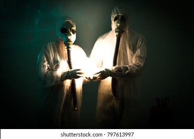 Two figures in biohazard suits and wearing gas masks hold a strange light.