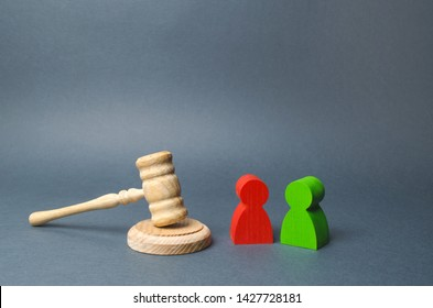 Two figures of people opponents stand near the judge's gavel. The judicial system. Conflict resolution in court, claimant and respondent. Court case, settling disputes. Legal advice, lawyer services.