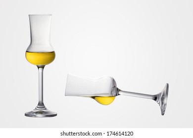 Two filled grappa glasses one levitating one is standing
