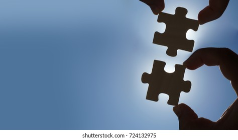 two finger try to connect couple of puzzle piece with sunset background.Jigsaw alone wooden puzzle against sun rays.one part of whole.symbol of association and connection. business strategy.copy space