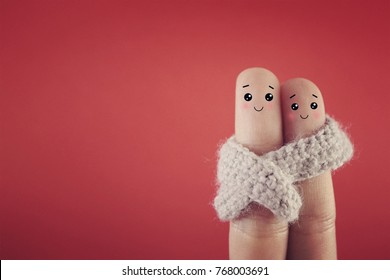 Two fingers decorated as a couple sharing a scarf.