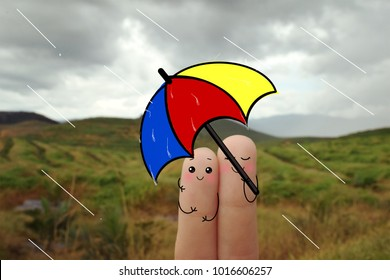 Two fingers decorated as lovely couple standing in the rain with an umbrella.
