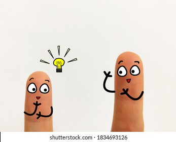 Two fingers are decorated as two person. They are discussing about new idea to develop their new business.
