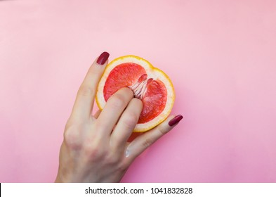 Two fingers on grapefruit on pink background. Sex concept.