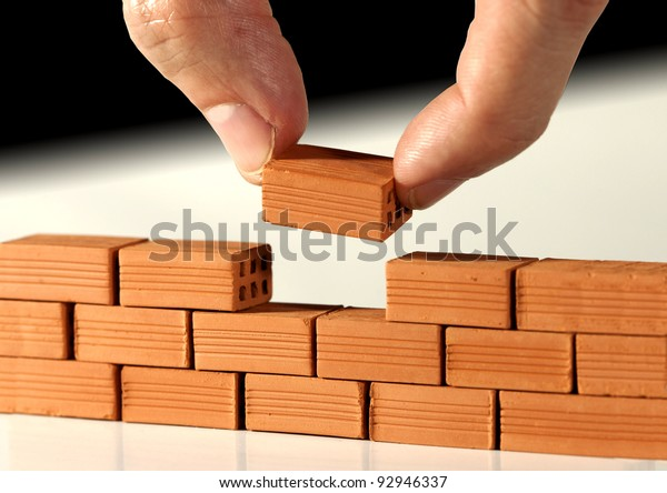 Two fingers put the last brick on the wall. Metaphoric scene
