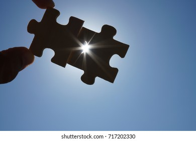 two fingers trying to connect couple puzzle piece with sunset background. Jigsaw wooden puzzle against sun rays.one part of whole.symbol of association and connection. business strategy