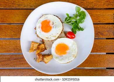 two fired eggs served with fired potato and salad.