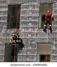 two firefighter climbing a wall of a house during the fire drill