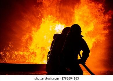 Zwei Feuerwehrleute, die Brandbekämpfungsdüsen zum Löschen von Feuer halten.Teamwork schießt Wasser, um die Gefahr von Brandkatastrophen zu verringern.Zugnotenteam.