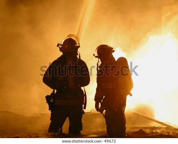 two firefighters hose down a blaze