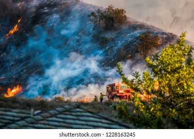 Two Firefighters Lean on Bulldozer with Burning Hillside in Back