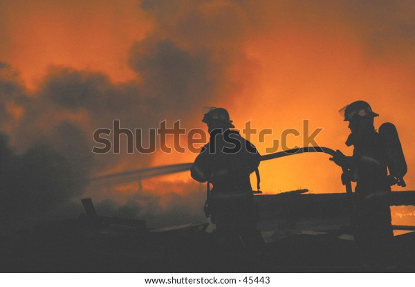 two firefighters are silhouetted at a fire