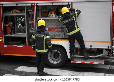 Two firefighters taking necessary equipment from the fire truck in hurry before they start off a rescue mission in Belgrade, Serbia. Translation: ''Firefighters Rescuers''