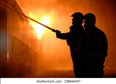 Two firefighters are trying to extinguish a hugh fire in a building