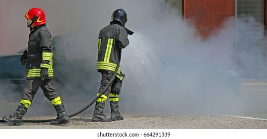 Two firefighters with uniform and protective helmet during a firefighting exercise