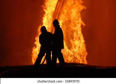 two firemen battling against raging fire, NOTE: top left corner particles are from fire and water spray, not camera noise