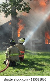 Two firemen direct a high pressure fire hose onto a burning farm house.