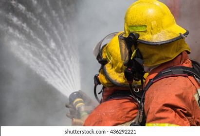 two firemen in helmet and oxygen mask spraying water to fire surround with smoke and dust