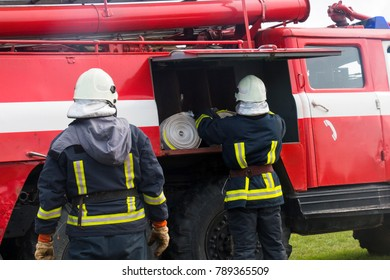 two firemen near the fire engine