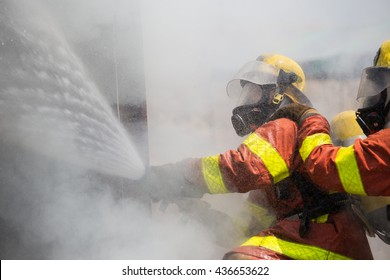 two firemen in oxygen mask helmet and fire fighting suit spraying water to fire surround with smoke and drizzle