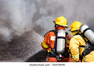 two firemen water spray by high pressure nozzle to fire surround with smoke and copy space