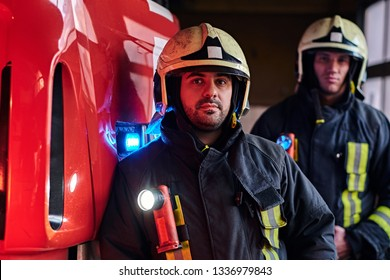 Two firemen wearing protective uniform standing next to a fire truck in a garage of a fire department. Arrival on call at night time
