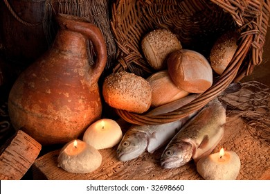 Two fish and five loaves of bread with candle-light and an antique wine jar