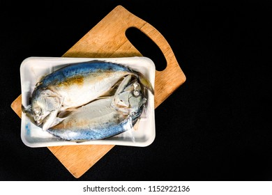 Two fish in packaging from supermaket on the wood plate.