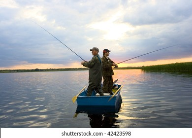 two fisherman on boat. catching pike