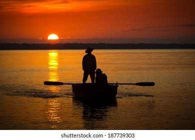 Two fishermen in a boat during sunset