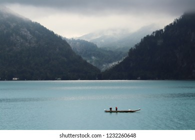 Two fishermen in a boat on a foggy morning on a crystal blue lake with mountains in the background. Taken at Attersee, Austria