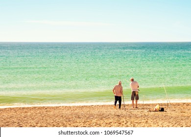 Two fishermen with fishing rods on the seashore. Rear view. Sunny summer day. Place for text.