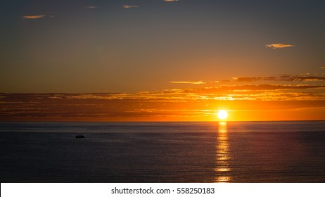 Two fishermen on a fishing skiff glide along the calm waters of the Sea of Cortez at sunrise off the coast of Los Barilles, Mexico.