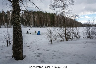 Two fishermen on the ice of a small river on a cloudy spring day and a small blue tent.