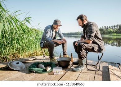 Two fishermen relaxing during the picnic on the wooden pier near the lake in the morning
